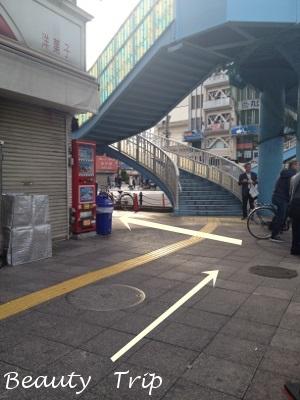 南北線の2番出口から出ると不動産屋の奥にある100円shopを左折します。